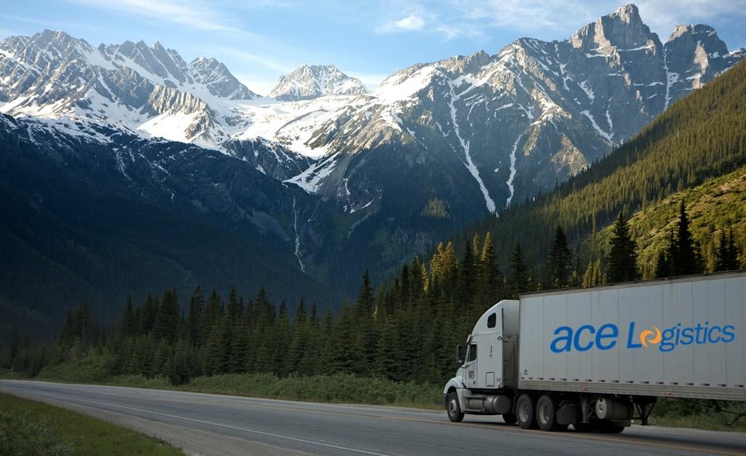 ace Logistics auto kravu pārvadājumi ar logo uz auto piekabes sāna, fonā kalni